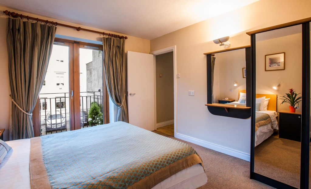 A comfy double bedroom in one of the Molesworth Court Suites